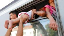 A migrant carries a young child in a train at the station in Beli Manastir, Croatia yesterday