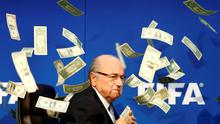 Banknotes are thrown at FIFA President Blatter as he arrives for a news conference  in July.