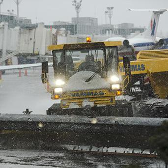 Ground crews clear the runway at LaGuardia Airport in New York (AP)