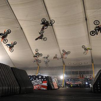 Riders back flip at the 02 Arena during a world record attempt for the greatest number of motorbikes back-flipping in the air simultaneously