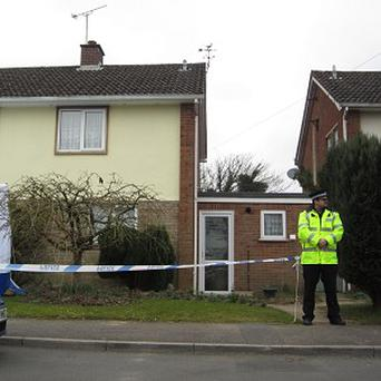 A policeman guards the property where a man was found shot dead alongside his partner on the Moonrakers cul-de-sac in Devizes, Wiltshire