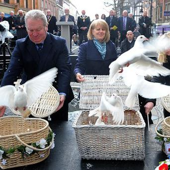 Wendy Parry, the mother of Tim Parry, releases doves with Mike Penning, Minister of State for Northern Ireland