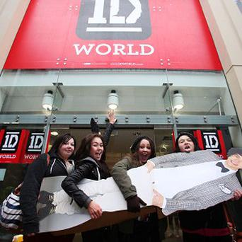 Fans outside the new 1D World pop-up shop in Leeds, with a cardboard cut-out of Harry Styles