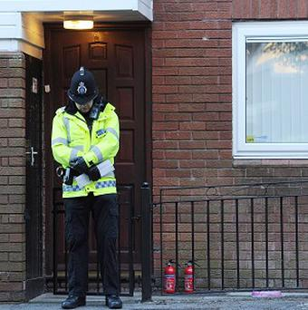 A police officer stands outside the front door of a house in Chaucer Grove, Atherton, where the body of a teenage girl was found