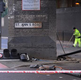 Workers clear the scene on the Seven Sisters Road in Haringey, north London, where two men died following a police chase