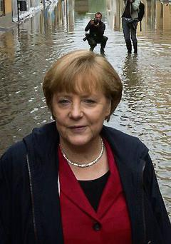 German Chancellor Angela Merkel speaks inspects a flooded street near the Elbe river in the east German town of Pirna