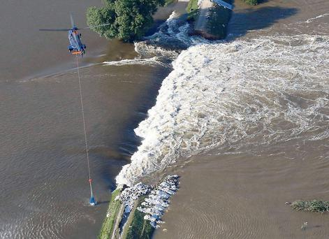 A Super Puma of the German Federal Police Bundespolizei carries sandbags to fix the broken dam built to contain the swollen Elbe river during floods near the village of Fischbeck, in the federal state of Saxony Anhalt