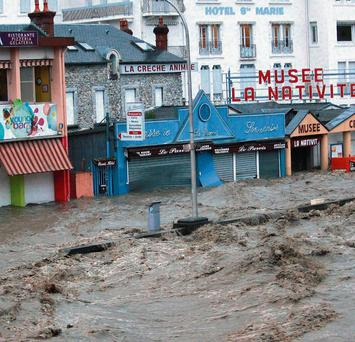 Shops in the center of Lourdes southwestern France, under water Tuesday, June 18, 2013. French rescue services and police are evacuating hundreds of pilgrims from hotels threatened by floodwaters from a rain-swollen river in the Roman Catholic shrine town of Lourdes.