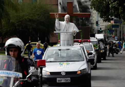 A statue of Pope Francis arrives with the World Youth Day cross to Rio de Janeiro city hall