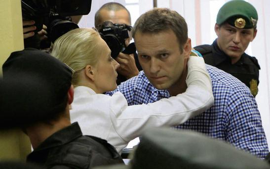 Russian protest leader Alexei Navalny (right) is embraced by his wife Yulia after being sentenced to five years in jail