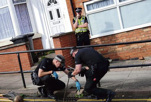 HUNT FOR CLUES: Police search near the scene of the house fire in Leicester that claimed the lives of a mother and her three children.
