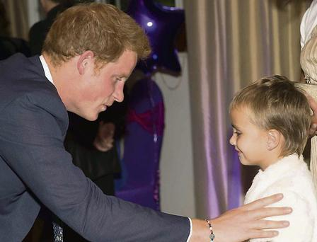 Prince Harry chatting to six-year-old Madison Kirk at an awards function at the Dorchester hotel in London last week