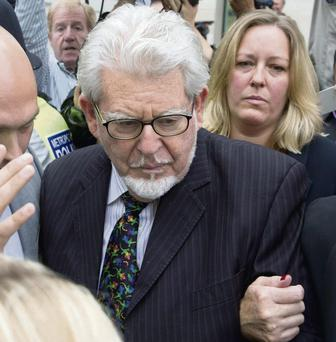 Entertainer Rolf Harris is surrounded by members of the media as he leaves Westminster Magistrates Court in central London