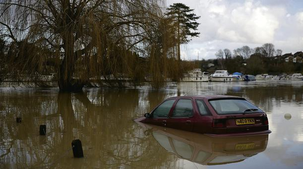 An abandoned car lies in floodwater in Tovil, Kent, England