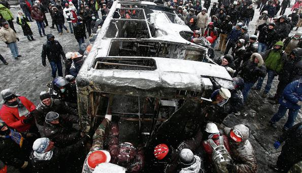 Demonstrators tug at a burnt vehicle during a rally