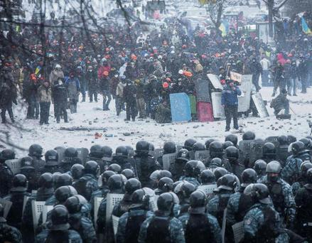 Riot police and interior ministry members stand in formation in front of pro-European protesters during clashes in Kiev yesterday