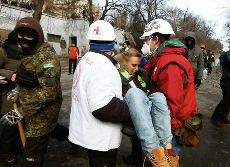 Medical volunteers carry a wounded journalist at the site of clashes in Kiev.
