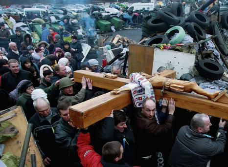 People carry a cross during a religious service at the site of the clashes in Kiev. Photo: DAVID MDZINARISHVILI