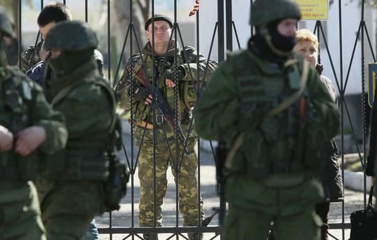 An armed Ukrainian soldier stands inside the gate of a Ukrainian military base as unidentified heavily-armed soldiers stand outside in Crimea