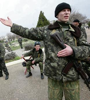 Ukrainian troops react as armed men in military uniform bloc the entrance of the Ukrainian military air base at the Bilbe