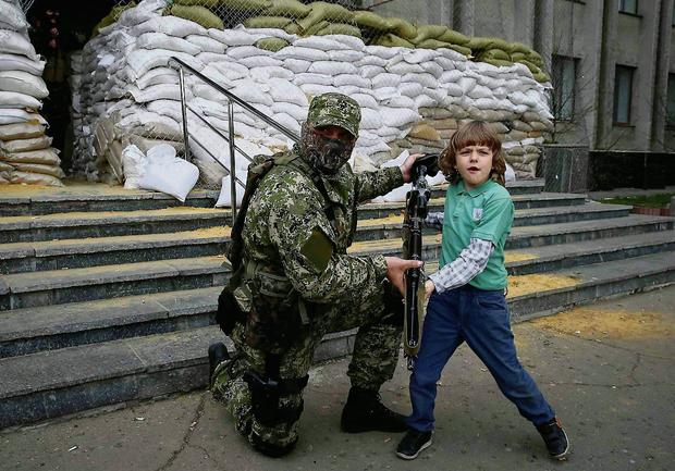 A pro-Russian armed man allows a local boy to hold a machine gun, while standing guard outside the mayor's office in Slaviansk. Photo: Reuters