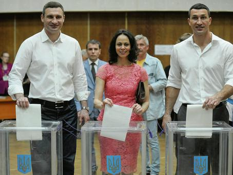 Vitali Klitschko, left, Kiev's mayoral candidate, his wife Natalia and his brother, boxer Wladimir Klitschko, cast their ballots at a polling station during presidential and mayoral elections in Kiev, Ukraine