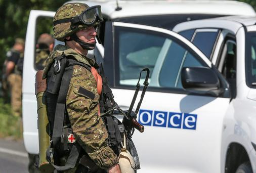 An armed pro-Russian separatist looks back next to a vehicle of the OSCE's monitoring mission in Ukraine, on the way to the site in eastern Ukraine where the downed Malaysia Airlines flight MH17 crashed, outside Donetsk