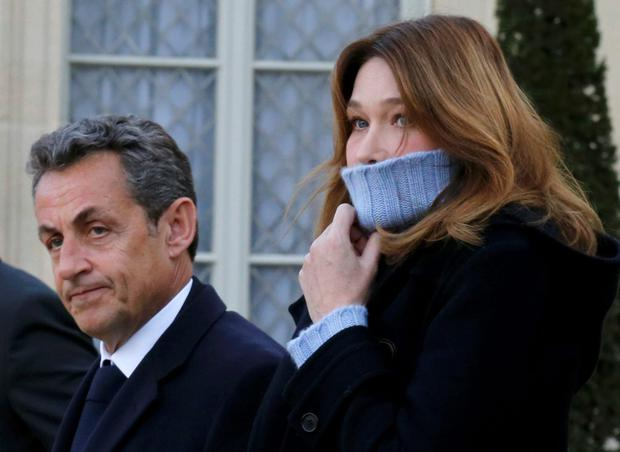 Former French President Nicolas Sarkozy, head of the French conservative party UMP party, and his wife Carla Bruni-Sarkozy arrive at the Elysee Palace before attending a solidarity march