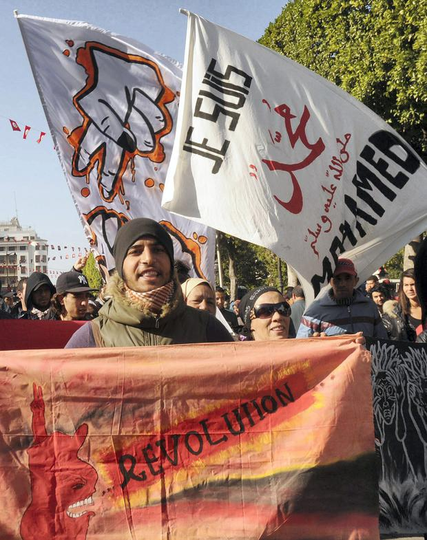Tunisian protesters shoot slogans against Charlie Hebdo and their new front cover during a rally in Tunis .