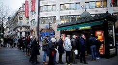 People queue to get a copy of satirical French magazine Charlie Hebdo new issue titled