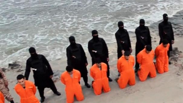 Men in orange jumpsuits purported to be Egyptian Christians held captive by the Islamic State (IS) kneel in front of armed men along a beach said to be near Tripoli