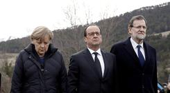 France's President Francois Hollande (C), Spain's Prime Minister Mariano Rajoy (R) and German Chancellor Angela Merkel walk on a field near the crash site of Germanwings Airbus A320 near Seyne-les-Alpes