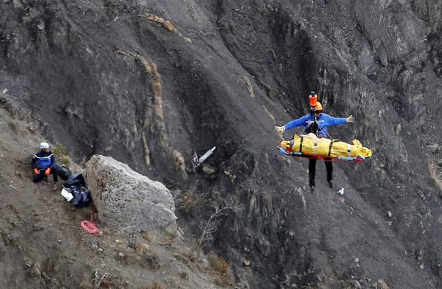 A rescue worker is lifted into an helicopter with what appears to be a body at the crash site near Seyne-les-Alpes, France.