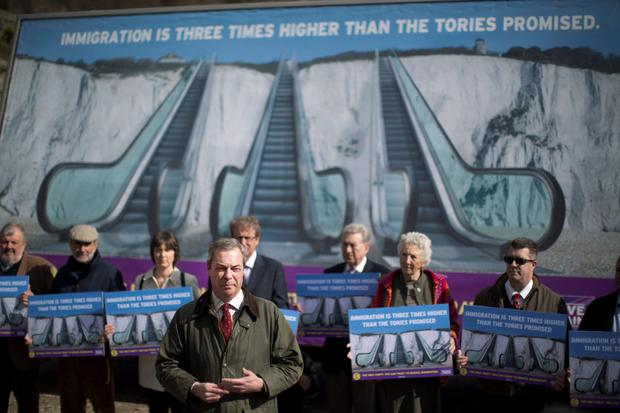 Nigel Farage the leader of the UK Independence Party (UKIP) speaks to the media backdropped by a poster unveiled for his party's immigration campaign launch for the British general election, in St Margaret's Bay, near Dover