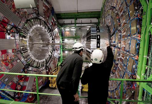 Workers examine the collider before it was restarted