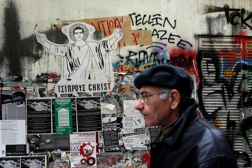 A pedestrian walks past a drawing of Greek Prime Minister Alexis Tsipras portrayed as Christ, with the words