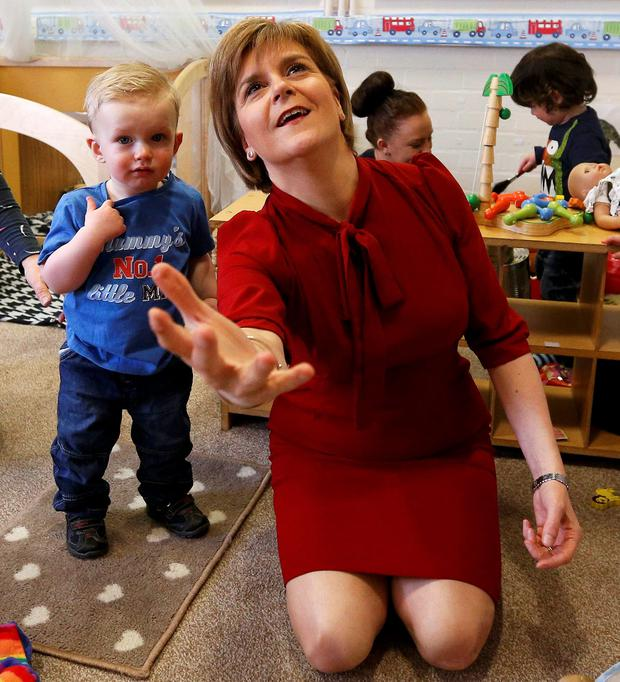 Scotland's first minister Nicola Sturgeon, watched by Patrick McVey, throws a ball at the Loanhead after-school club and community nursery in Edinburgh
