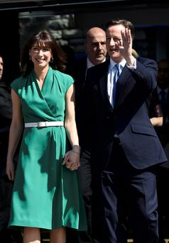 Britain's Prime Minsiter David Cameron holds his wife Samantha's hand as he waves after launching the Conservative Party's election manifesto in Swindon yesterday.