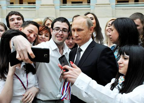 Russian president Vladimir Putin poses for pictures with call-centre employees after the live broadcast of the nationwide call-in in Moscow. Photo: Reuters