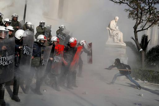An anti-establishment protester tries to attack riot police during a protest in Athens yesterday.
