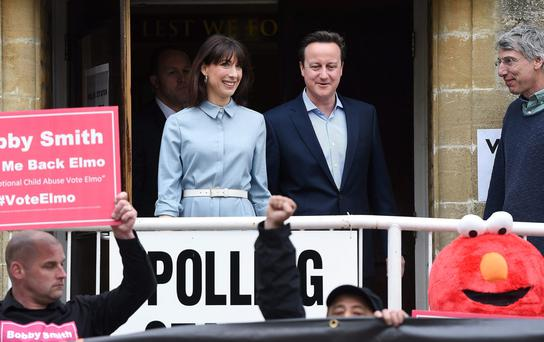 British Prime Minister David Cameron looks at 'Fathers For Justice' protesters as he exits a polling station after voting with his wife Samantha (C-L), at the village of Spelsbury in Oxfordshire.