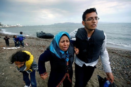 An Afghan immigrant family lands at a beach on the Greek island of Kos after crossing a portion of the south-eastern Aegean Sea between Turkey and Greece on a dinghy