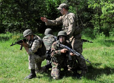 A US soldier, right, instructs Ukrainian soldiers during joint training exercises on the military base in the Lviv region, western Ukraine yesterday.