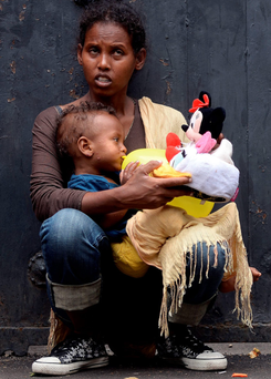A mother holds her child with toys brought by aid workers outside a migration centre in Rome, where hundreds of migrants have arrived recently