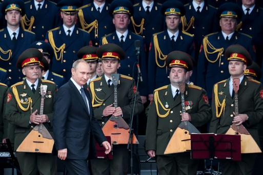 Russian President Vladimir Putin, foreground, leaves a podium after delivering his speech at the opening of the Army-2015 international military show features the latest Russian weapons in Kubinka, outside Moscow, in Russia yesterday.