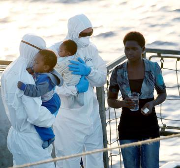 Crew members on thel LE Eithne with children during an operation as they rescue refugees in the ongoing humanitarian mission in the Mediterranean.