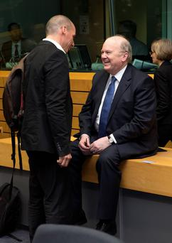 Greek Finance Minister Yanis Varoufakis (L) talks with Michael Noonan