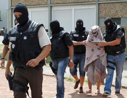 French police forces escort a woman from a residential building during a raid in Saint-Priest, near Lyon