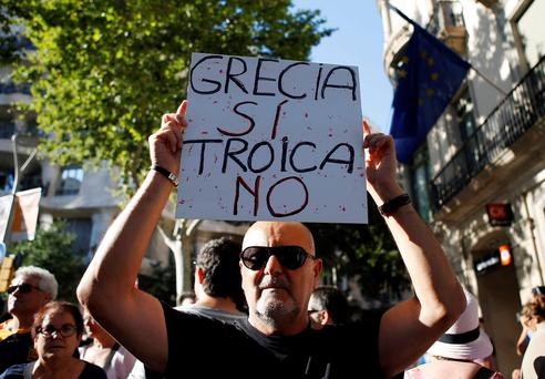 A man holds a banner supporting Greece during a protest in front of the European Union office in Barcelona, Spain. The banner reads