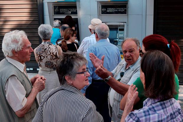 Pensioners discuss politics while waiting at a national bank's ATM to withdraw some money in the Greek capital Athens yesterday